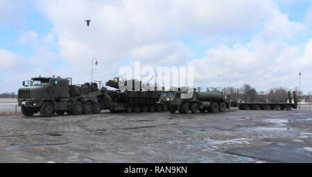 LOWCHOWSKA, Pologne - un système de transport d'équipement lourd transporte un Américain M1A2 Abrams tank à travers la Pologne pour vérifier principales voies d'approvisionnement capable de déplacer un M1A2 Abrams tank à travers l'écart de Suwalki, la porte d'entrée des pays baltes, le 22 février 2017. Le convoi qui a débuté le 20 février en Allemagne en route vers l'Estonie. Banque D'Images