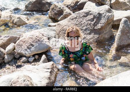 Heureux femme portant un maillot de bain assis dans Sacajawea Hot Springs en Arkansas, une des sources chaudes naturelles près d'une rivière Banque D'Images