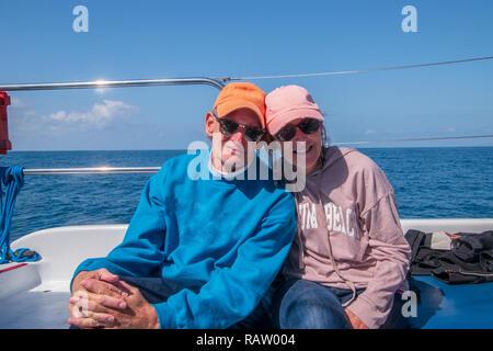 Couple heureux d'caucasian baby-boomers assis sur un bateau avec le bleu de l'eau dans l'arrière-plan. Les deux portant des sweat-shirts, casquettes de baseball et chanté Banque D'Images