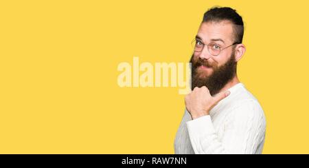 Jeune homme portant des lunettes et hipster chandail d'hiver avec sourire heureux face à la recherche et en pointant sur le côté avec le pouce vers le haut.