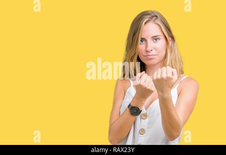 Belle jeune femme sur fond isolé prêt à combattre avec fist, geste de défense en colère et contrarié face, peur de problème Banque D'Images