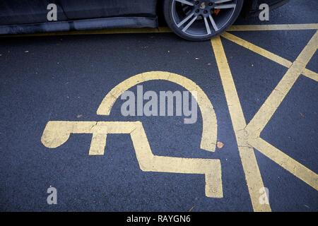 Une roue mal garée empiéter sur l'espace nécessaire aux personnes à mobilité réduite Parking gratuit Banque D'Images