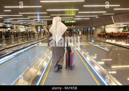 Passagers arabes sur tapis roulant au terminal de l'Aéroport International Hamad moderne à Doha, Qatar