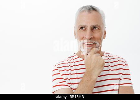 Un homme intelligent et créatif avec les cheveux gris et sa barbe se frottant le menton avec un large sourire ravi en regardant en haut à gauche, en pensant avoir idée intéressante qui pose en t-shirt à rayures Banque D'Images