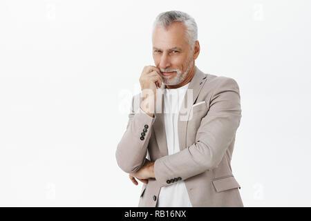Smart et tricky enthousiastes vieil homme à barbe blanche et sèche crossing main contre la poitrine et les lèvres toucher smiling curieusement et loucher de l'intérêt à l'idée ou l'intention d'avoir l'appareil photo Banque D'Images