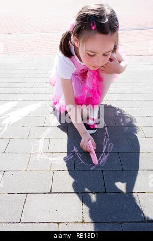 Belle petite fille dessinant un coeur rose avec de la craie sur le trottoir. Banque D'Images