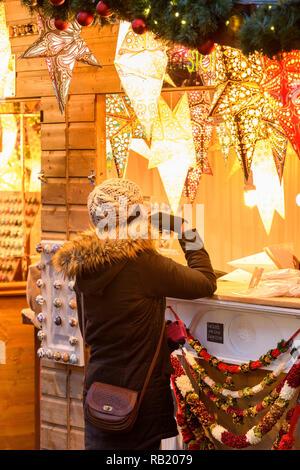 Femme au Marché de Noël (client potentiel) à la star du papier à l'éclairage (lanternes) sur l'affichage, le moulage des golden glow - York, England, UK.