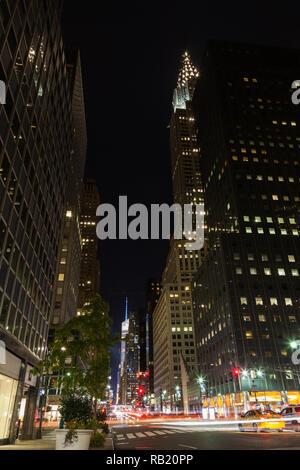 La vue le long de la 42e Rue, New York. Le Chrysler building peut être vu de nuit permanent au-dessus les bâtiments voisins. Banque D'Images