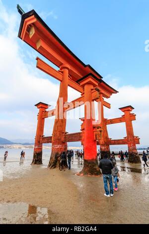 Le Japon. Le Grand Torii au sanctuaire Shinto d'Itsukushima sur l'île de Miyajima à marée basse avec une foule de gens autour de sa base de six piliers. Banque D'Images