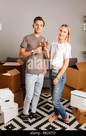 Photo de jeune couple avec des verres à vin parmi les commandes de boîtes de carton Banque D'Images