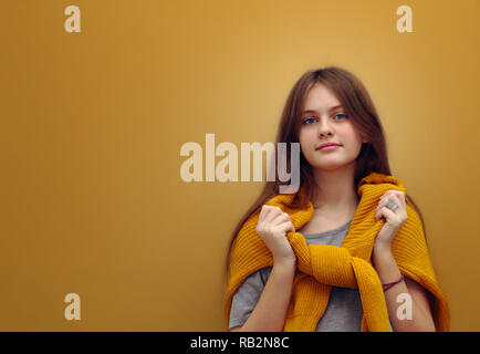 Brune aux yeux bleus jeune fille timide aux longs cheveux dans un pull sur un fond brun