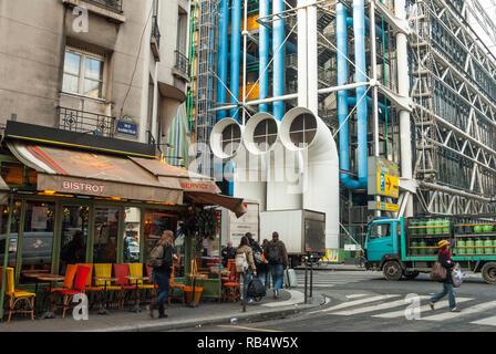 Scène de rue de Paris, l'hiver, en contraste avec le style ancien de l'architecture parisienne d'un petit café à côté de l'architecture radicale du Centre Pompidou. Banque D'Images