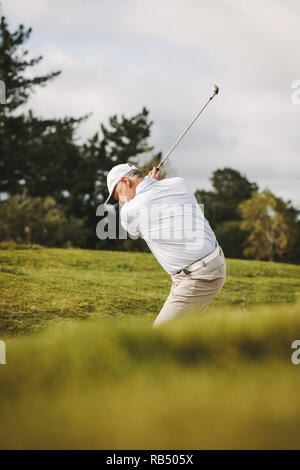 Golfeur aîné professionnel jouer au golf sur le parcours. L'homme de frapper la balle d'un bunker de sable.
