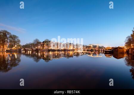 Les Pays-Bas, Amsterdam, Canal et péniches le long de la rivière Amstel. Pont maigre droit. À l'aube. Banque D'Images