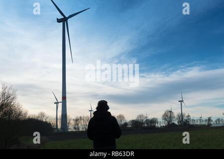 L'homme en face d'une ferme éolienne utilise protecteur de bruit pour réduire le bruit de l'éolienne Banque D'Images