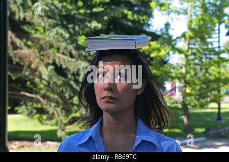 Brunette woman balancing un livre sur la tête , Banque D'Images
