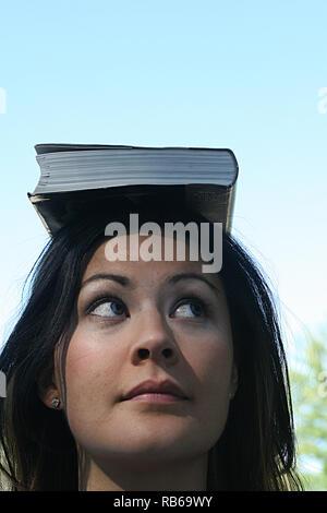 Brunette woman balancing un livre sur la tête. Banque D'Images