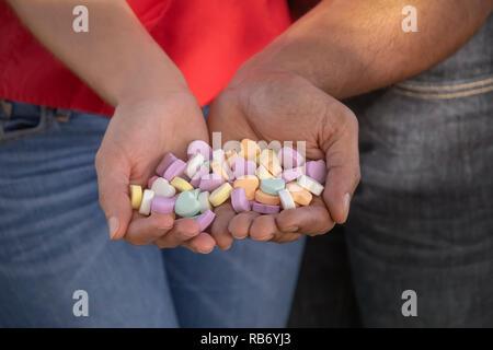 Ils tiennent l'un l'autre à proximité de façon à ne pas laisser tomber l'une des forme de coeur coloré Valentines Day candy. Banque D'Images