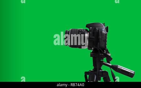 Sur trépied appareil photo DSLR et fond vert isolé Banque D'Images
