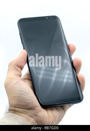 Main tenant le Samsung Galaxy S8 Plus smart phone découper sur un fond blanc Banque D'Images