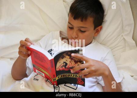 Garçon de 11 ans à lire au lit dans le Salento, en Italie. Banque D'Images