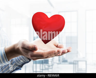 Concept d'amour et de passion avec cœur rouge dans les mains des hommes. Technique mixte Banque D'Images