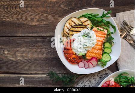 Saumon grillé, tomates et aubergines avec le quinoa et sauce tzatziki sur fond de bois rustique. Dîner sain. Vue d'en haut.