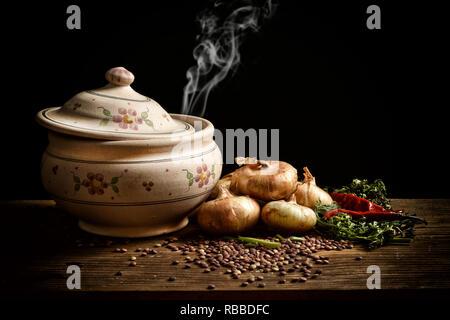 Soupe de lentilles dans le bol en terre cuite avec des ingrédients autour sur fond noir - libre Banque D'Images