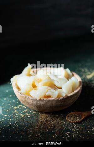 Libre de certaines bandes de morue salée dessalée dans un bol en terre cuite rustique, sur un tableau vert foncé, l'ingrédient principal de préparer le xato catalan, un Banque D'Images