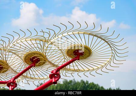 Livraison côté ou râteaux andaineurs roues à charrier soulevé du sol contre le ciel bleu. Râteaux utilisé pour réduire le temps de séchage et conservation de débris de wi Banque D'Images