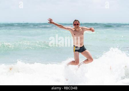 Jeune homme heureux sauter de haut avec bras levés forme en rouge maillot maillot et splash wave plantage à Miami Beach en Floride dro l'eau verte Banque D'Images