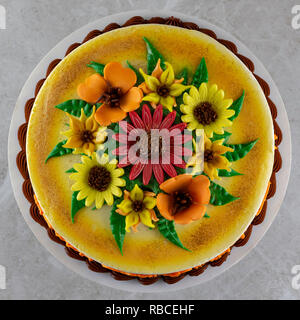 Passage tiré d'un gâteau décoré avec du fondant fleurs et saupoudré de paillettes comestibles. Banque D'Images