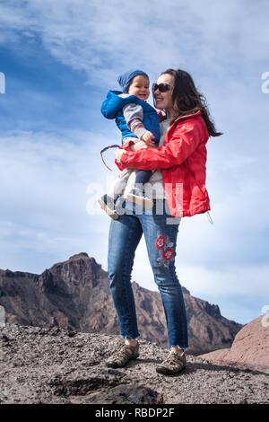 Une belle photo d'une belle femme et son fils debout sur une montagne de l'arrière-plan d'un ciel nuageux