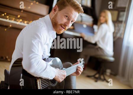 Homme jouant de la guitare acoustique avec belle jeune femme qui joue du piano Banque D'Images