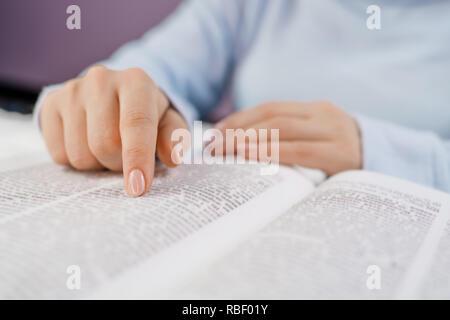 En étudiant la bibliothèque du collège de la préparation aux examens. L'apprentissage, la gratitude, la religion concept. Méconnaissable woman reading gros livre - Sainte Bible et prier. Christian l'étude des écritures.