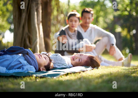 Deux enfants asiatiques little boy and girl having fun lying on grass avec les parents assis à regarder en arrière-plan. Banque D'Images
