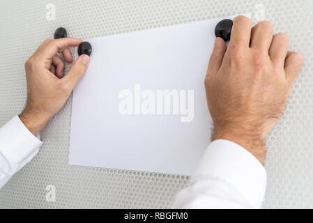 Vue rapprochée du businessman clipping feuille de papier blanc vierge avec deux aimants noir sur blanc tableau magnétique. Banque D'Images