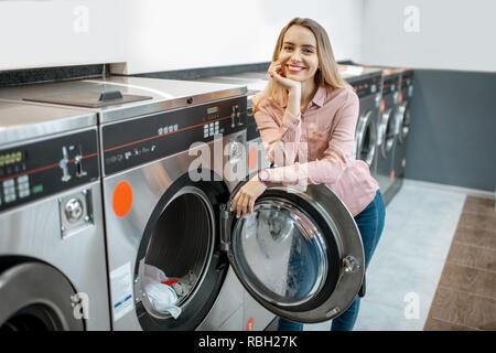 Portrait of a young smiling woman standing au self-service de blanchisserie publique Banque D'Images