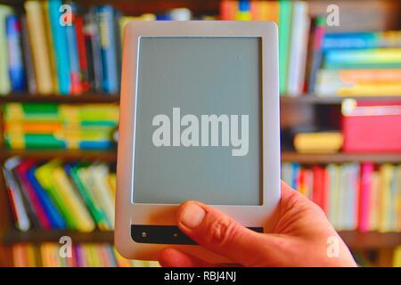 Du livre électronique ou numérique appareil Tablette de lecture. E-livre dans la main de l'homme. Sur l'arrière-plan est l'étagère avec des livres réels. Livres en ligne concept Banque D'Images