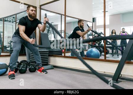 Athletic homme barbu musculaire l'exercice dans la salle de sport avec bataille des cordes. Le sport, la formation, les gens, le mode de vie sain concept Banque D'Images