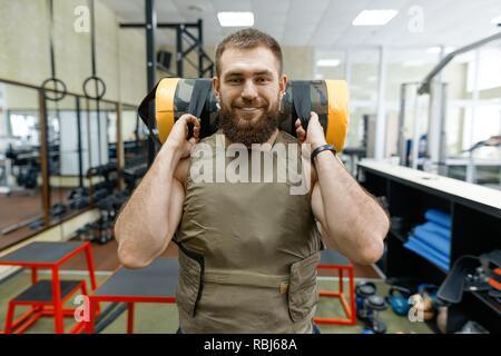 Portrait Portrait musculaire homme barbu habillé en veste pondéré dans la salle de sport, style militaire. Banque D'Images