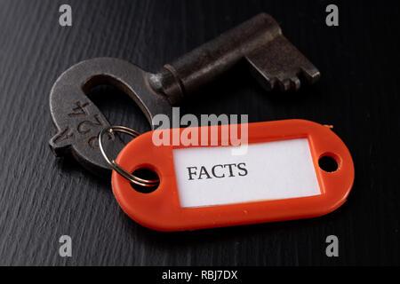 Une vieille clé avec une inscription sur un tableau noir. Accessoires et le symbole faisant référence à ce mot dans la description de la clé. Fond noir. Banque D'Images