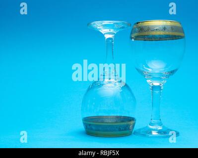 Deux verres de vin vide sur fond bleu. Un verre est à l'envers, de bas en haut Banque D'Images