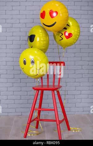 Gray appartement studio avec chaise, mur de brique jaune, rouge emoji ballons détails chaise. Banque D'Images
