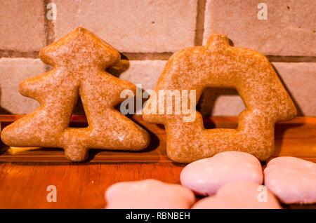 Pains de Noël en forme d'arbre de Noël et une maison rose avec peu de cookies sur le comptoir de la cuisine Banque D'Images