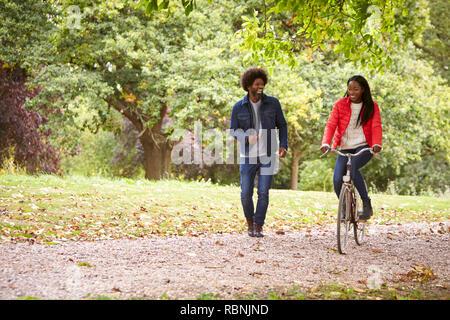 Black couple s'amusant dans un parc, le woman riding a bike, front view