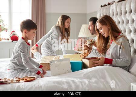 L'ouverture des cadeaux de leurs parents les enfants comme ils sont assis sur le lit l'échange de présents le jour de Noël Banque D'Images