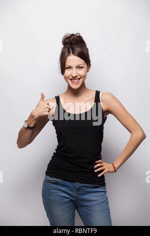 Happy smiling beautiful brunette woman showing Thumbs up geste, isolé sur fond blanc. Banque D'Images