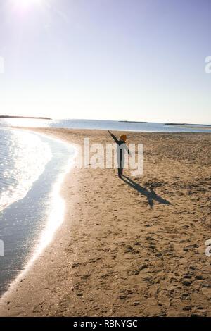 6 ans avec les cheveux rouges et jaunes woolly hat, marche vers la caméra avec ses bras tendus, faisant semblant de voler sur une plage ensoleillée à Palavas les Flot Banque D'Images