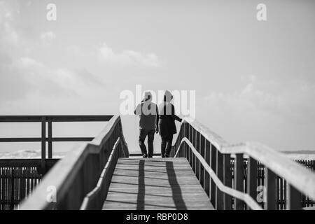 Vue arrière de l'homme et de la femme marchant sur trottoir de bois, Odeceixe, Portugal Banque D'Images